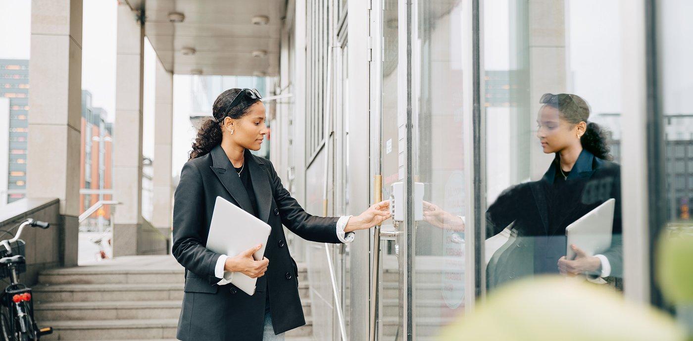Kvinne taster inn kode på inngangsdør til kontorbygg