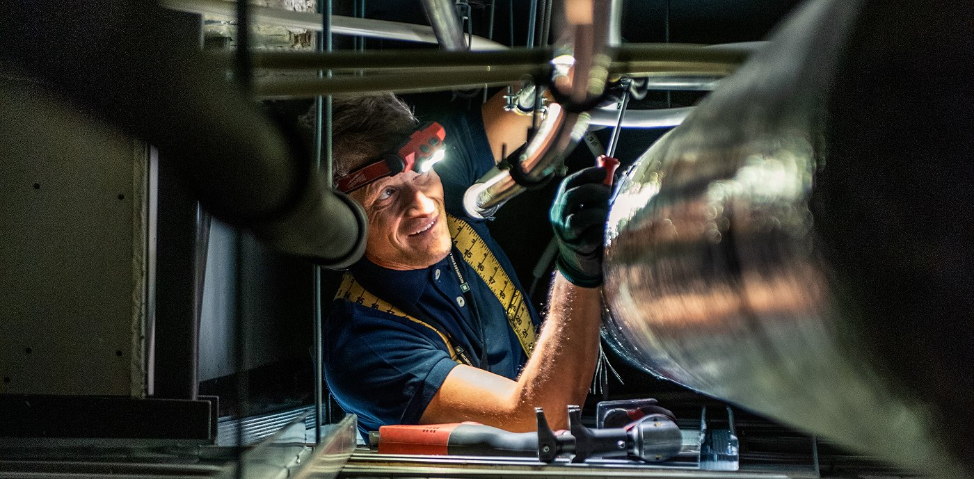 Nærbilde av rørlegger som utfører kontroll på teknisk anlegg med hodelykt