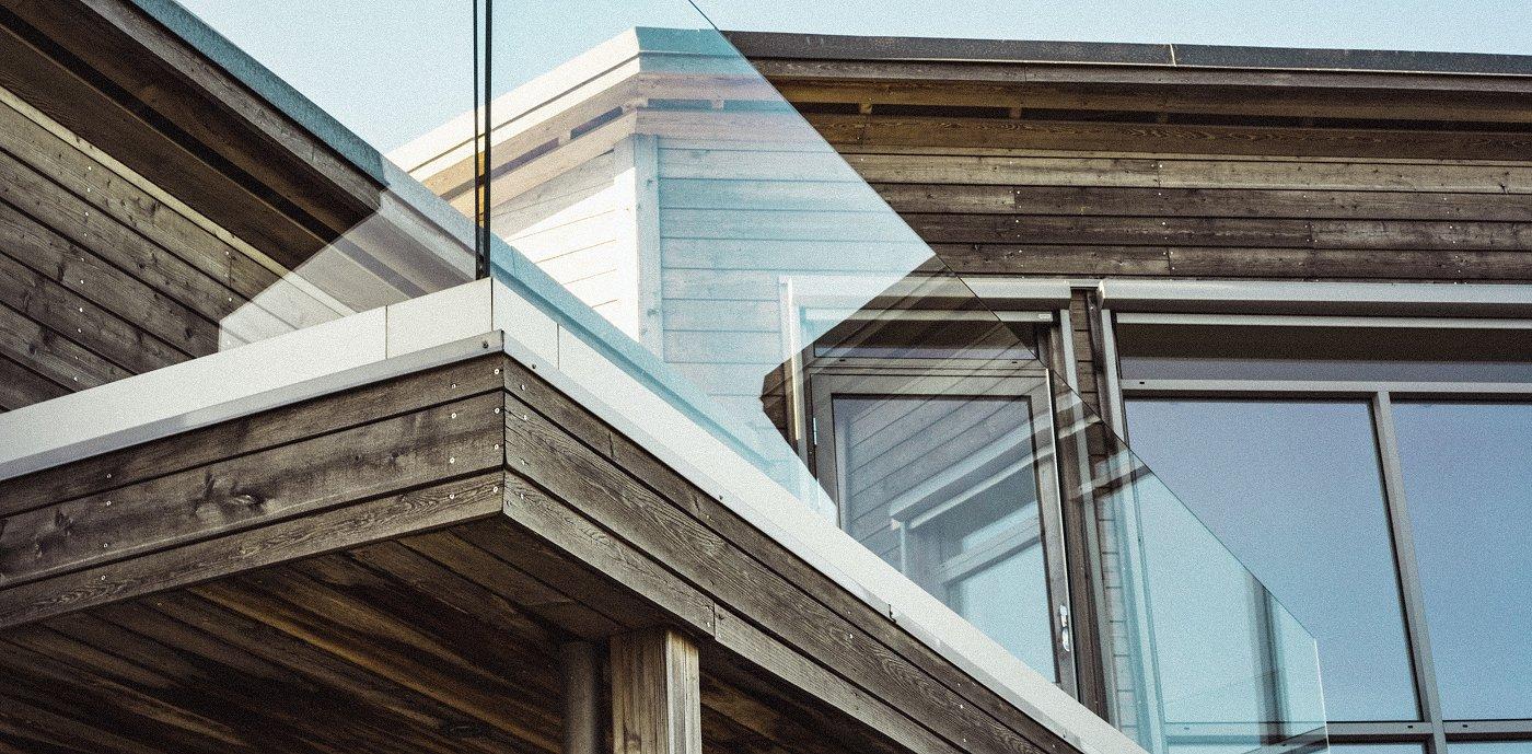 Nærbilde av enebolig med rekkverk i glass på balkong